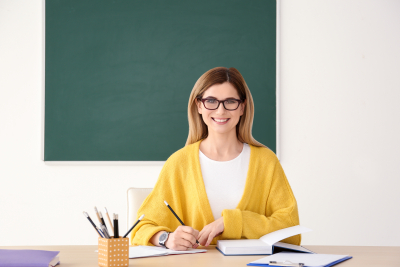 Young female teacher working at table in classroom